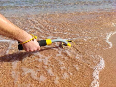The photo of an underwater metal detector vel on the sand.Treasure searching and tourist adventure background.