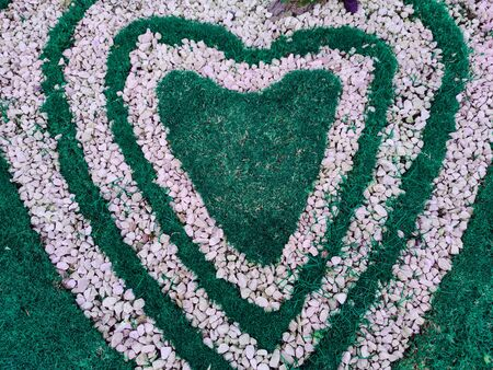 Top view of heart shape white stones on the grass for landscape design. Backdrop for Valentine's day or romantic background for wedding post card or marketing advertisment