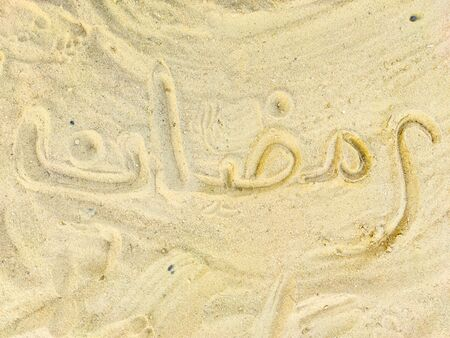 Ramadan word in Arabic, handwriting on the sand, lettering.