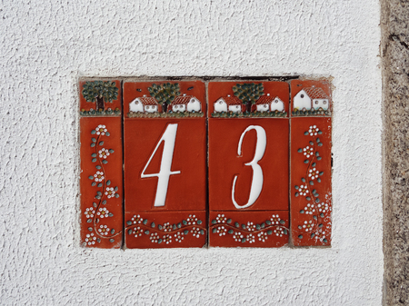 Tiled red house number 43 on the white stucco wall