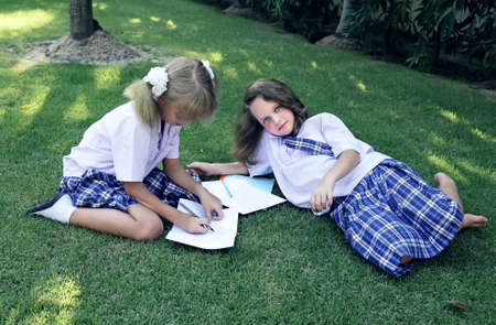 Schoolgirls rest lying on the grass photo