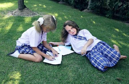 school children uniform: Schoolgirls rest lying on the grass Stock Photo