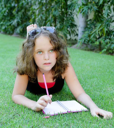 Beautiful girl with a notebook on the grass  She is looking up and dreaming  photo