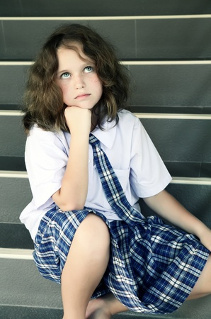 fed up: Tired schoolgirl on the stairs Stock Photo