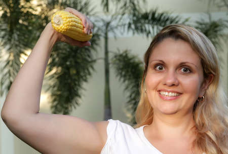 Happy overweight woman has workout with corn. With as a dumbbell . photo