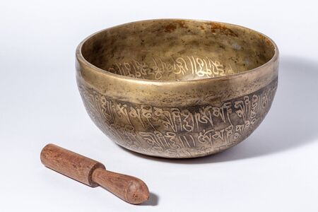 Tibetan singing bowl with percussion stick. White background. Stock Photo