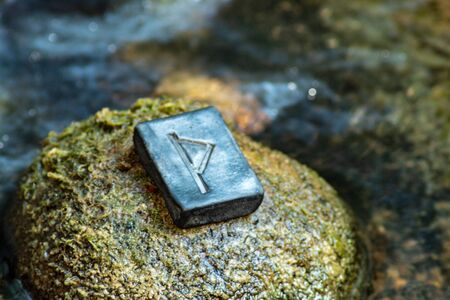Norse rune Thurisaz (Thurs) on the stone and the evening river background. The strength and defense of a warrior. Male sexuality. Courage. Runa Thurisaz is associated with the Scandinavian God Thor.