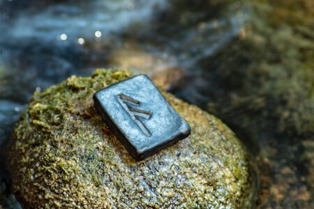 Norse rune Ansuz on the stone and the evening river background. The voice of God. Freedom. Verbal and sound signs. Rune Ansuz is associated with the supreme Scandinavian God Odin. Banco de Imagens