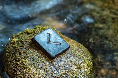 Norse rune Kennaz on the stone and the evening river background. Knowledge, decision, way out of a difficult situation. Helps to work with any data and information.