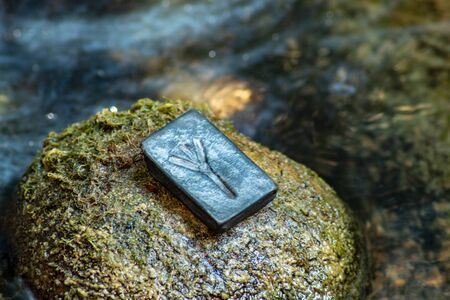 Norse rune Algiz on the stone and the evening river background. Protection, help of the Gods.