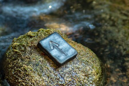 Norse rune Teihwaz (Tihwaz,Tyr) on the stone and the evening river background. Law, order, protection, nobility, courage. The rune is associated with the Scandinavian god Tür. Фото со стока