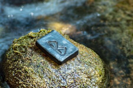 Norse rune Bercana on the stone and the evening river background. Birch, femininity, motherly care and protection. The rune is associated with the Scandinavian Goddess Frigg. Banco de Imagens