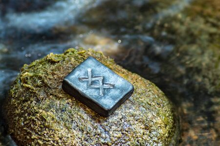Norse rune Ingwaz on the stone and the evening river background. Seed, potential, energy, fertility. The rune is associated with the Scandinavian god Freyr. 免版税图像