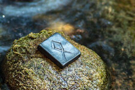 Rune nordique Othala (Odal) sur la pierre et le fond de la rivière du soir. Maturité des hommes, famille, foyer, tradition, protection des biens. La rune est associée au dieu scandinave suprême Odin. Banque d'images