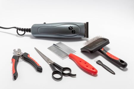Pets care kit: pet trimmer, metal brush, metal comb, scissors, claw cutters, small brush for cleaning. Isolated on white background. Imagens