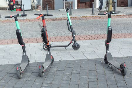 Four electric scooters are parked by the road in city center.