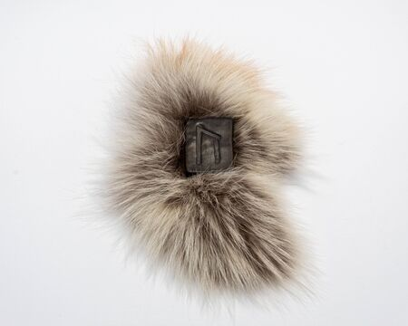 Norse rune Uruz, isolated on fur and white background. Health, strength, masculinity. The energy of the earth.