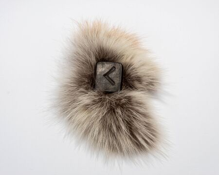 Norse rune Kennaz, isolated on fur and white background. Knowledge, decision, way out of a difficult situation. Helps to work with any data and information. Stock Photo