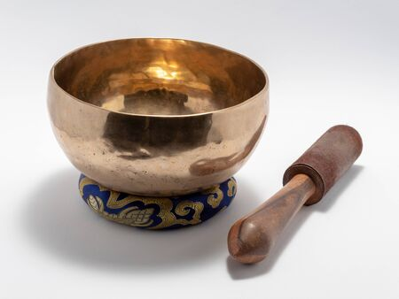 Tibetan singing bowl with a percussion stick on a special pad. Isolated on a white background. Stock Photo