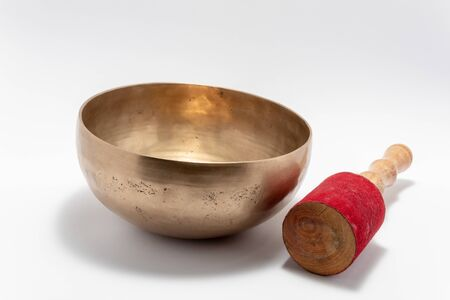Tibetan singing bowl with percussion stick. Isolated on white background.
