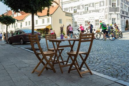 Czech Republic, Mikulov - August 30, 2019. Despite the end of summer, the tourist season is still in full swing. A table of a cozy street cafe is waiting for its visitors. Cyclists in the background.