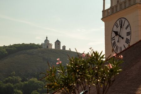 A small chapel on a hill in the backlight. In the foreground are tower clocks and flowers. Chapel of St. Sebastian. Mikulov, Czech Republic.