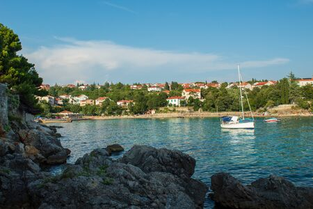 Seascape: rocky coast, turquoise water, yacht, the city in the background. Krk, island of Krk, Croatia. Stok Fotoğraf