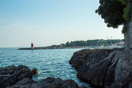Seascape: rocky coast, turquoise water, a lighthouse and a beach in the background. Krk, island of Krk, Croatia.
