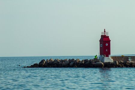 Seascape: turquoise water, evening sky, lighthouse close-up. Krk, island of Krk, Croatia.