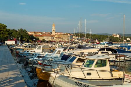 Fishing boats at the pier and a view of the old city. Krk, island of Krk, Croatia.