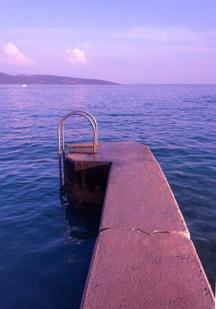 A stone platform for swimmers to go down to the sea. A little way to summer fun :) Krk, island of Krk, Croatia. Stok Fotoğraf