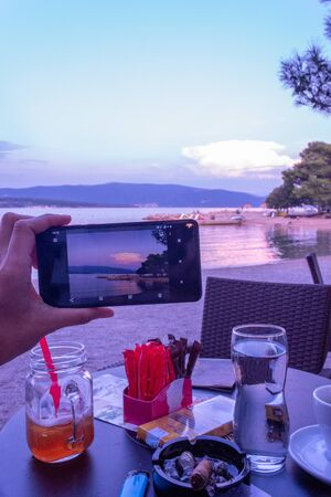 A picture of the evening seascape on a smartphone from a small cafe on the beach. Krk, island of Krk, Croatia.