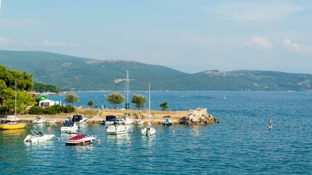Seascape: rocky coast, turquoise water, small boats and yachts, mountains in the background. Krk, island of Krk, Croatia.