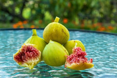 Juicy slices and whole fig fruits on a glass table. Close-up, blurred background.