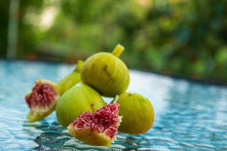 Juicy slice and whole fig fruits on a glass table. Close-up, blurred background.