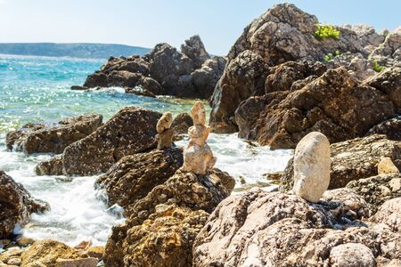 Seascape: small stone pyramids on large stones, turquoise sea, blue sky. Krk, island of Krk, Croatia. Stok Fotoğraf