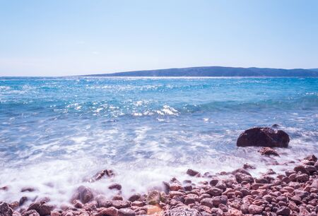 Seascape: rocky beach, calm turquoise water with a soft silk effect, blue sky. Krk, island of Krk, Croatia. Stok Fotoğraf