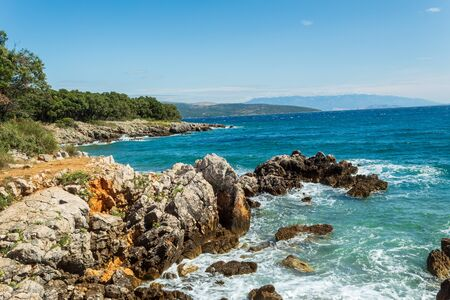 Seascape: rocky coast, stones, green forest, calm turquoise water, blue sky. Krk, island of Krk, Croatia.