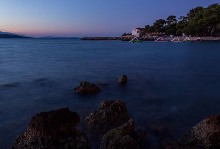 Dawn on the beach. The effect of silk water. Blue and cyan tones. Krk, island of Krk, Croatia. Stok Fotoğraf