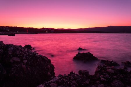 Dawn on the beach. The effect of silk water. Purple and yellow tones. Krk, island of Krk, Croatia. Stok Fotoğraf