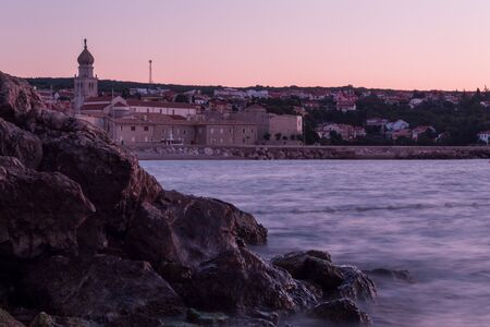 The pier of the old city at dawn. Rocky ledge in the foreground. The effect of silk water. Krk, island of Krk, Croatia.