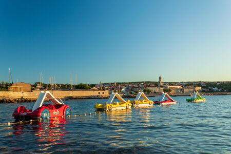 Racing car-shaped water bikes in the morning sun. Krk, island of Krk, Croatia. Stok Fotoğraf