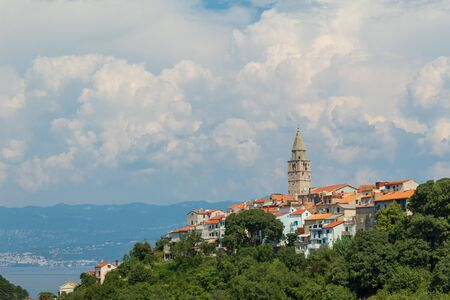 Landscape of the ancient city. Clouds, sea, old town on a hill. Vrbnik, island of Krk, Croatia.