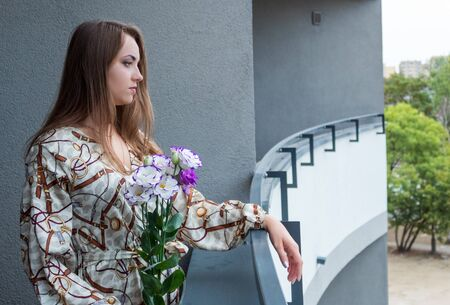 A young, beautiful, thoughtful girl in a dress and with flowers in her hands stands on the balcony of a multi-floor house.