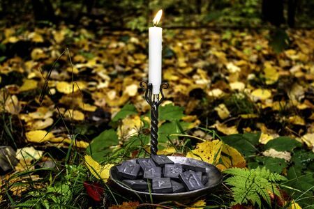 Norse runes in a forged bowl with a candle on the background of autumn forest foliage. 免版税图像