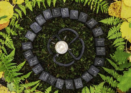 A circle of 24 Scandinavian runes on the background of moss and leaves in the autumn forest. In the center of the circle is a forged candleholder with a candle.