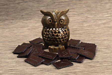 Norse handmade brown leather runes. Wooden figure of Owl inside of the composition.