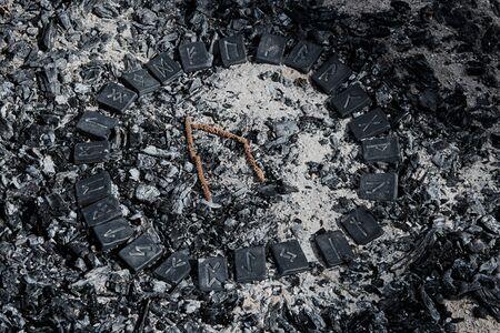 Norse rune Uruz on ashes backgorund inside the circle of 24 Norse runes