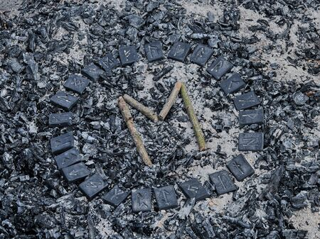Norse rune Ehwaz on ashes backgorund inside the circle of 24 Norse runes Stock Photo