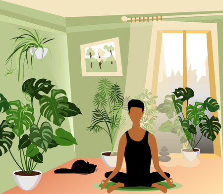 man meditates sitting in the living room surrounded by flowers and a cat